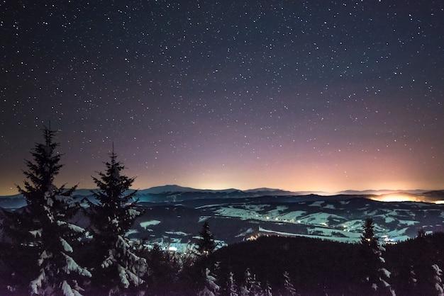 Prachtig betoverend landschap van nachtelijke winterhellingen onder de sterrenhemel en het noorderlicht. noordelijke natuur schoonheid concept. copyspace