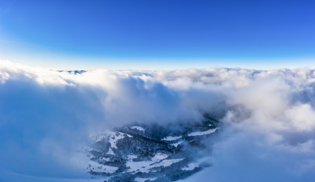 Prachtig betoverend uitzicht op bergen en rotsen met sparrenbos op een ijzige winteravond met mist en zonsondergangzon. hard winter natuur concept