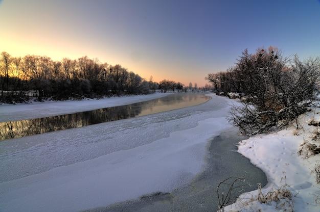 Prachtig betoverend uitzicht op de rivier die aan het begin van de lente smolt met bomen langs de kust op een koele lenteavond