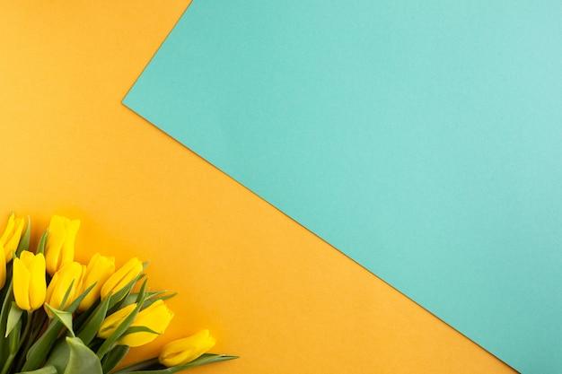 Prachtig bloemstuk. gele bloementulpen, leeg kader voor tekst op een gele achtergrond. bruiloft. verjaardag valentijnsdag. moederdag. plat lag, bovenaanzicht, kopie ruimte