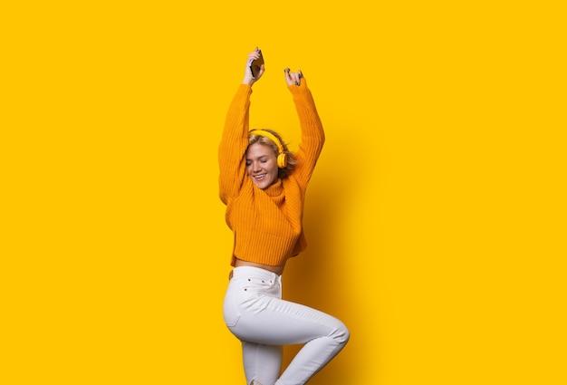 Prachtig blond kaukasisch meisje gekleed in een oranje trui en witte spijkerbroek is dansen terwijl poseren op een gele achtergrond en luisteren naar muziek