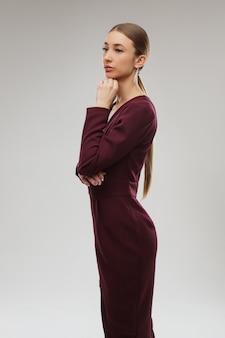 Prachtig blond meisje in eenvoudige jurk en zwarte hakken.