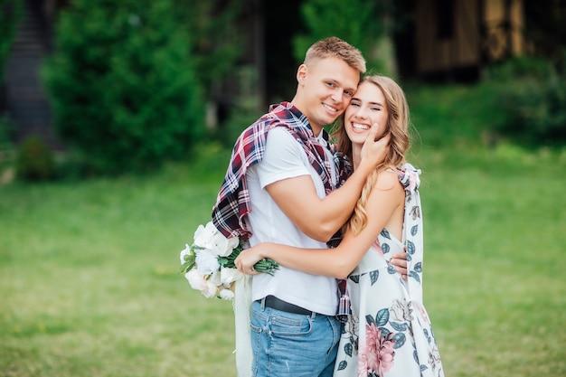 Prachtig blond meisje knuffelt en lacht op een zonnige dag met haar aantrekkelijke man
