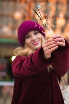 Prachtig blond meisje met gloeiende bengaalse lichten op de kerstmarkt in kiev. vervagingseffect