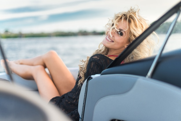 Prachtig blond meisje rustend op een jacht