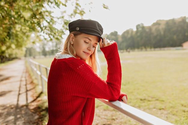 Prachtig blond model dat zich kalm voelt in het zonnige herfstweer. jonge vrouw trendy hoed met mooie accessoires dragen.