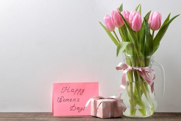 Prachtig boeket bloemen van roze tulpen in een vaas en een geschenkdoos en de tekst van een gelukkige vrouwendag tegen een grijze muur