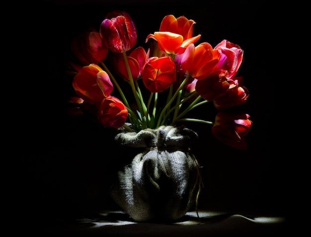 Prachtig boeket felrode tulpen in een vaas met jute