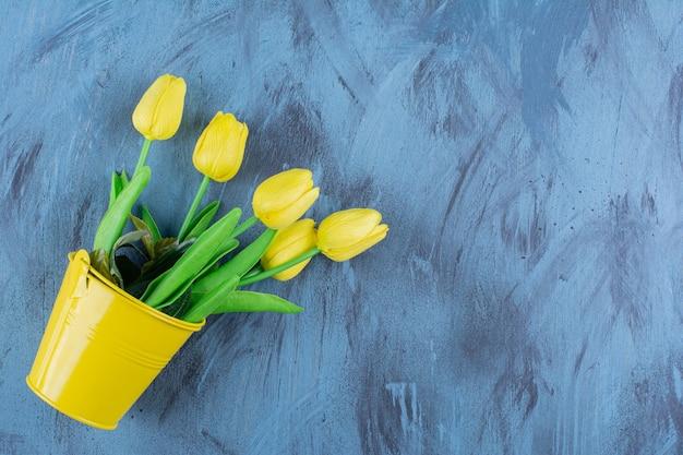 Prachtig boeket verse gele tulpen op blauw