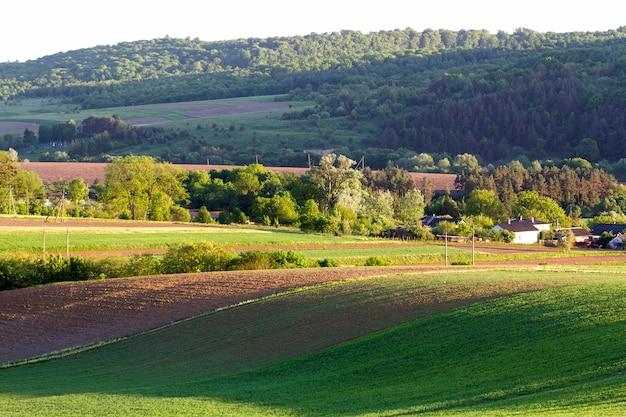 Prachtig breed panorama van geploegde en groene velden met groeiende tarwe onder heldere heldere blauwe hemel op rustige dorp en verre heuvels bedekt met bos achtergrond. landbouw en landbouw concept.