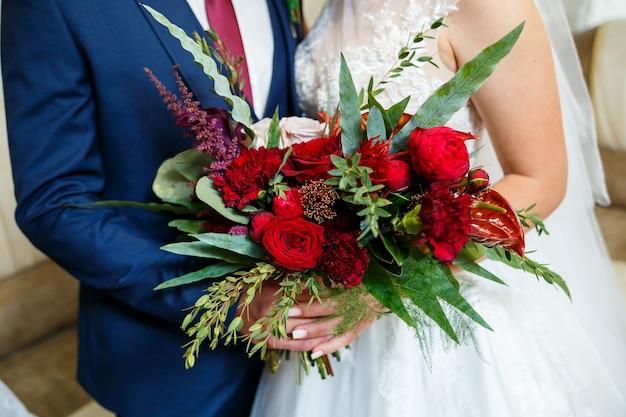 Prachtig bruidsboeket bloemen in de handen van de pasgetrouwden
