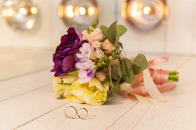 Prachtig bruidsboeket en trouwringen in een ongewoon interieur tegen de achtergrond van lampen