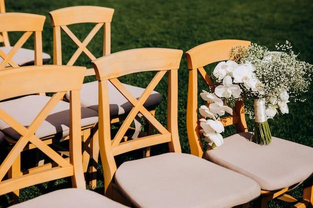 Prachtig bruidsboeket versierd met orchideeën op een stoel voor de ceremonie