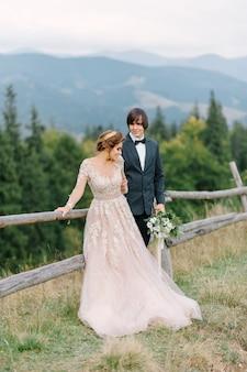 Prachtig bruidspaar zoenen en omhelzen in de buurt van de oever van een bergrivier met stenen