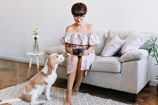 Prachtig brunette meisje in een stijlvolle jurk met behulp van internet terwijl haar beagle hond spel wacht. indoor portret van drukke dame in glazen met tablet in de buurt van grappige puppy