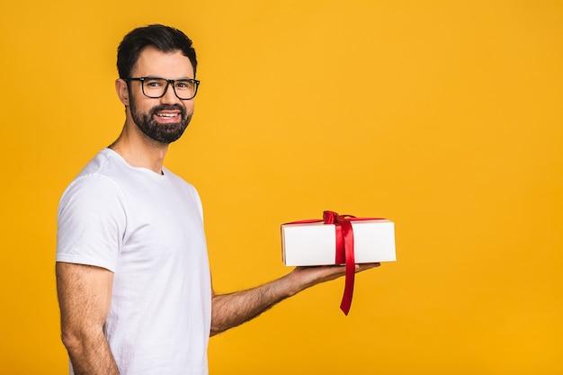 Prachtig cadeau! schattige foto van aantrekkelijke bebaarde man met mooie glimlach met verjaardagscadeau doos geïsoleerd op gele achtergrond.