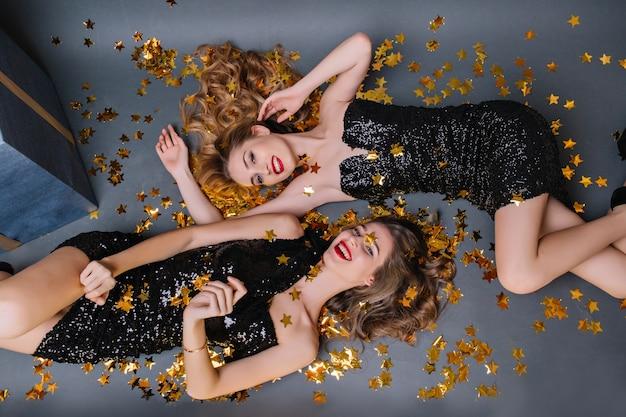 Prachtig donkerharig meisje in zwarte jurk liggend onder confetti en lachen met zus. binnenportret van schattige dames in luxe kleding die genieten van feestfotoshoot.