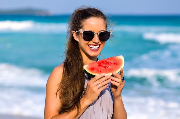 Prachtig donkerharige meisje in zonnebril poseren in sea resort in zomervakantie. openluchtportret van donkerbruin vrouwelijk model dat watermeloen houdt en weg oceaanachtergrond bekijkt.