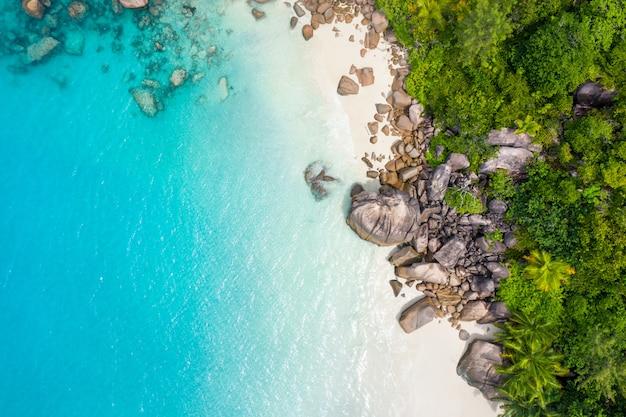Prachtig eiland in de seychellen. la digue, anse d'argent strand. water stroomt, en golven schuimen op een tropisch landschap