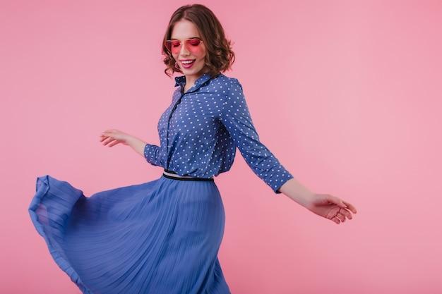 Prachtig europees meisje dansen met een geïnspireerde glimlach. indoor portret van aantrekkelijke vrouw in lange blauwe rok.