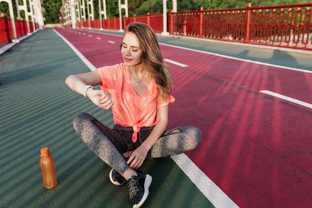 Prachtig europees meisje in zwarte sneakers kijken naar haar polshorloge. outdoor portret van schattige jonge vrouw die zich voordeed op sintelbaan met sap.