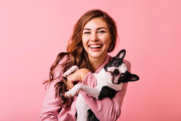 Prachtig europees vrouwelijk model chillen met puppy. indoor portret van debonair meisje genieten van portretshoot met haar schattige huisdier.
