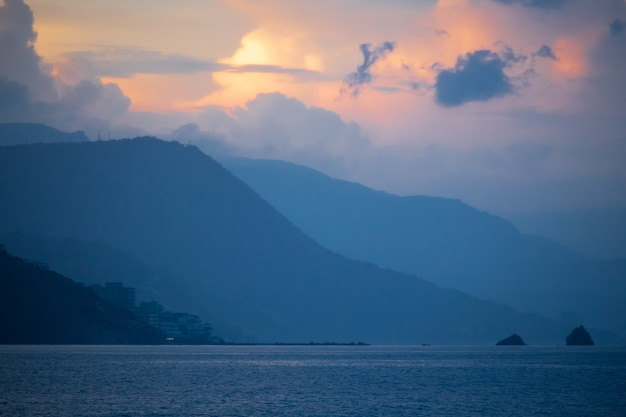 Prachtig fantastisch zeegezicht pastel oranjeblauwe kleuren gelaagde bergen en kalme zee kopieer de ruimte