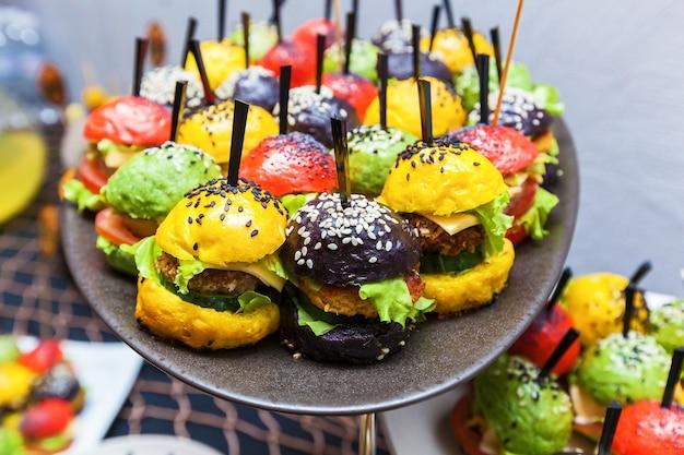 Prachtig gedecoreerde horeca bankettafel met verschillende gekleurde hamburgers