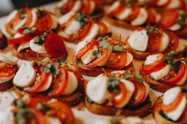 Prachtig gedecoreerde horeca feesttafel met verschillende hapjes en hapjes met sandwich, kaviaar, vers fruit.