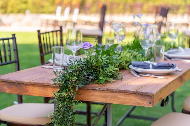 Prachtig gedecoreerde houten tafel in een zomers openlucht café. groene tak en verse bloemen tafeldecoratie.