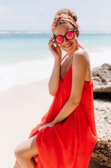 Prachtig gelooid meisje in zomerjurk poseren op het strand. buiten schot van extatische lachende vrouw zittend op grote steen op het strand.