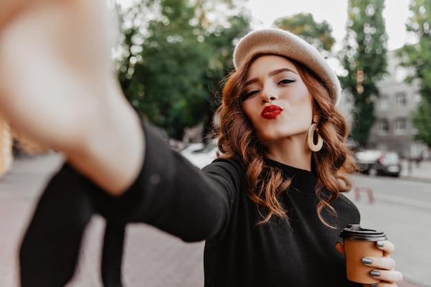 Prachtig gember frans meisje selfie maken. buiten schot van sierlijke krullende dame met kopje cappuccino.