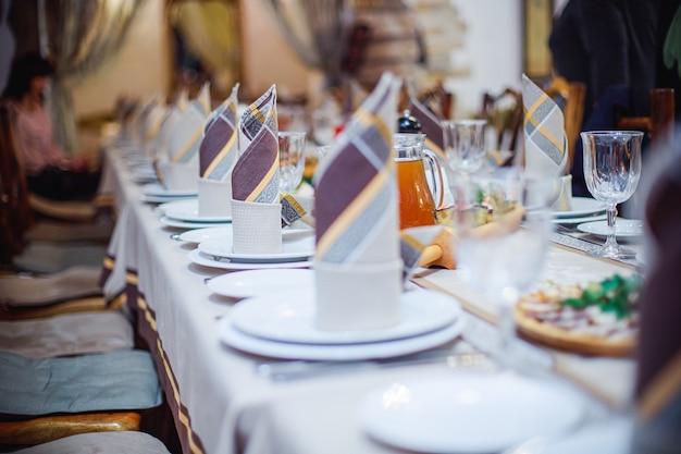 Prachtig gevouwen servetten op een gediende tafel. bruine servetten op een witte plaat. viering in het restaurant. caféfeest bij het banket.
