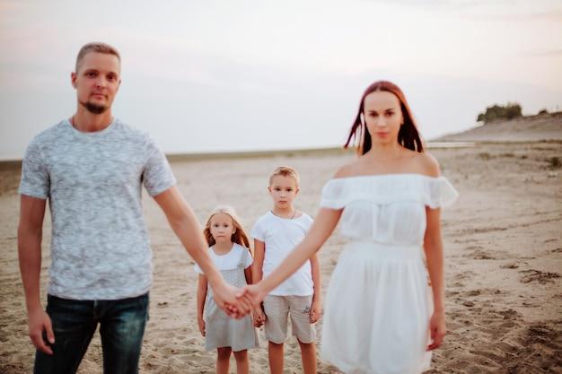 Prachtig gezin met twee kinderen op een zandstrand. zachte focus. focus op kinderen.