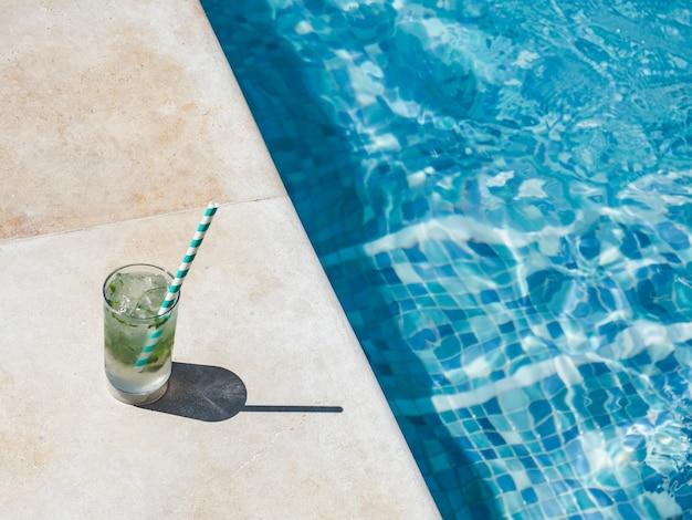 Prachtig glas met een verfrissende cocktail op de achtergrond van het zwembad