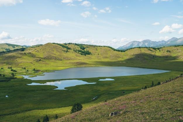 Prachtig groen berglandschap met meersysteem op plateau tussen bosheuvels. toneellandschap met merengroep op plateau. blauw merensysteem en kanalen in brede vallei. systeem van bergmeren