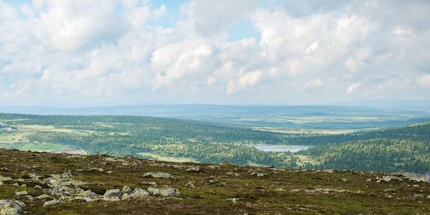 Prachtig groen landschap omgeven door bergen onder een bewolkte hemel