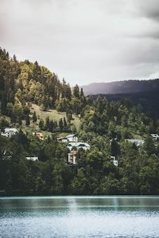 Prachtig helder meer met een paar huizen gebouwd op een heuvel