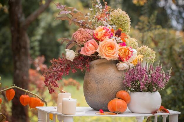 Prachtig herfstdecor met bloemen, bessen, pompoenen in de tuin