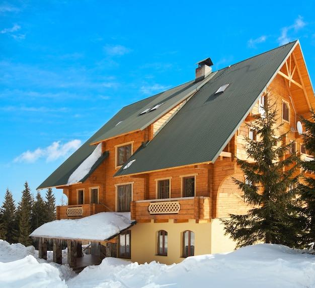 Prachtig houten huis op een pittoresk winterresort op een blauwe hemelachtergrond