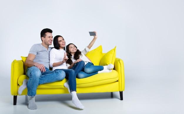Prachtig jong gezin ontspannen op een bank en een gezamenlijke selfie maken in hun grote moderne appartement.