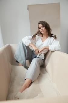 Prachtig jong meisje met blote voeten zittend in zand in studio
