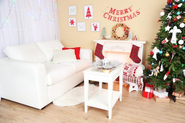 Prachtig kerstinterieur met bank, sfeerhaard en dennenboom