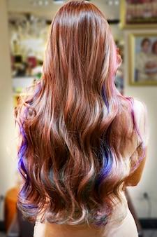 Prachtig krullend haar na geverfd met veel kleuren en gekruld in professionele salon