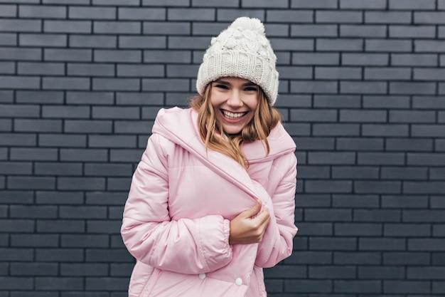 Prachtig lachend meisje poseren in roze jas. buiten foto van opgewonden blonde dame in trendy winter hoed.