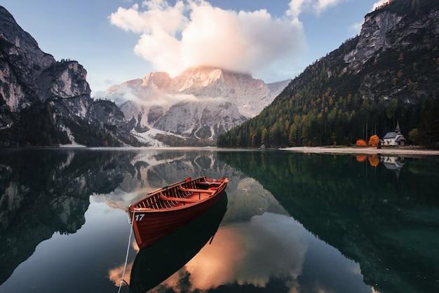 Prachtig landschap. houten boot op het kristalmeer met majestueuze erachter berg. reflectie in het water. kapel ligt aan de rechter kust