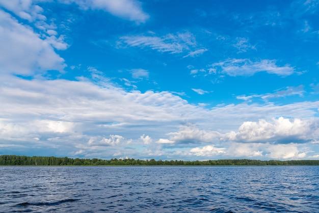 Prachtig landschap met blauwe rustige lege rivieroppervlak met kabbelend oppervlak onder heldere blauwe hemel met pluizige witte wolken op mooie zonnige zomerdag.