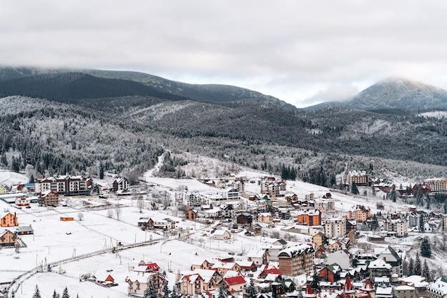 Prachtig landschap met sparrenbos en de eerste sneeuwval bij het dorp. veel huizen staan op de winterheuvels. seizoenen concept