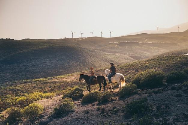 Prachtig landschap op de berg met windmolens en een paar mensen die paard rijden voor een excursie op een alternatieve levensstijl van een cowboyboerderij - zonlicht en heldere lucht