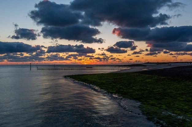 Prachtig landschap van een adembenemende zonsondergang boven de kalme oceaan in westkapelle, zeeland